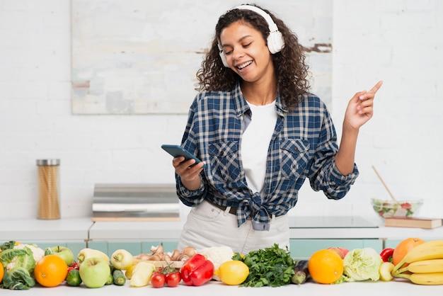 Vrouw het luisteren muziek en het dansen in keuken