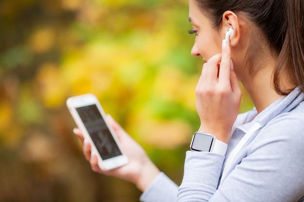 Vrouw het luisteren muziek, het doen van trainingoefeningen op straat