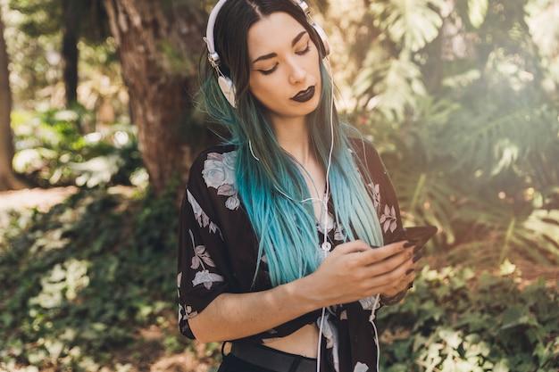 Vrouw het luisteren muziek op hoofdtelefoon die mobiele telefoon doorbladeren