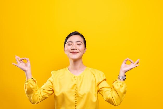 Vrouw het mediteren die haar houden dient yogagebaar op geïsoleerde gele muur in