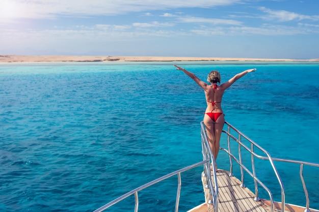 Vrouw het ontspannen bij de neus van het cruiseschip met open wapens