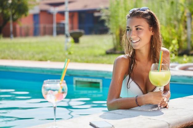 Vrouw het ontspannen en drink een cocktail bij zwembad