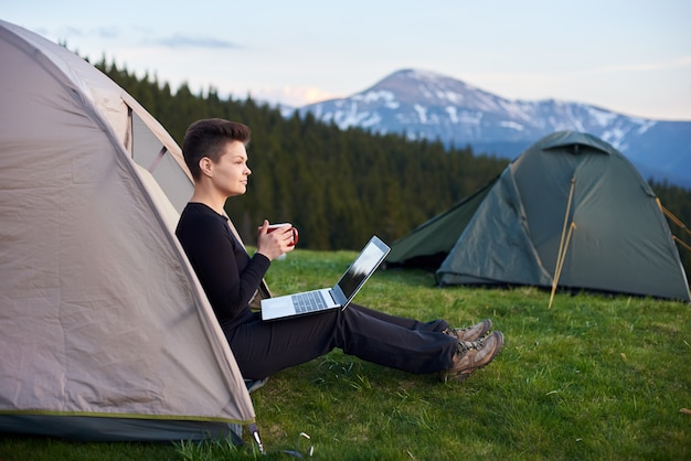 Vrouw het ontspannen in haar tent op de het kamperen plaats die een kop houden weg kijkend