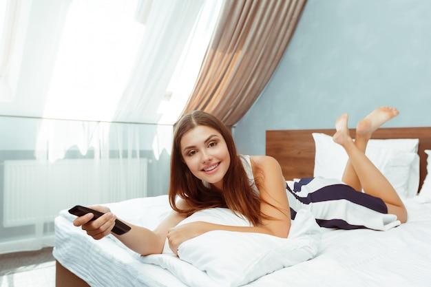 Vrouw het ontspannen in hotelruimte en het kijken tv