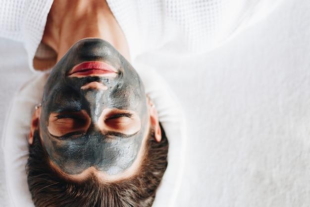 Vrouw het ontspannen met een houtskool gezichtsmasker