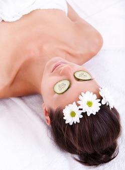 Vrouw het ontspannen met plakjes komkommer op haar ogen
