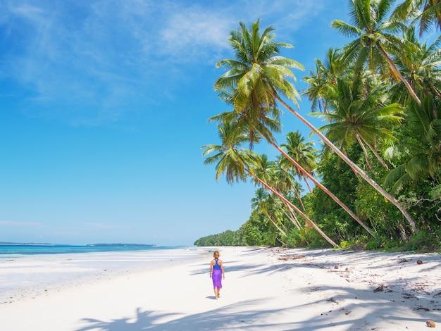 Vrouw het ontspannen onder het varenblad van de kokospalm op toneel wit zandstrand, zonnige dag, turkoois transparant water, echte mensen. indonesië, kei-eilanden, molukken maluku, wab-strand