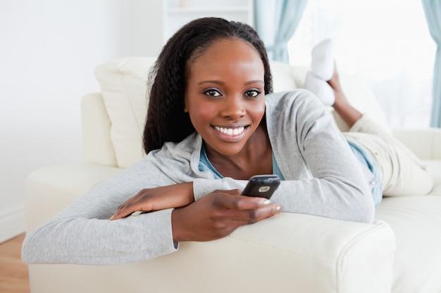Vrouw het ontspannen op bank terwijl het texting