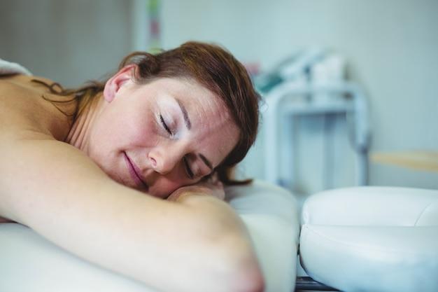 Vrouw het ontspannen op onderzoeksbed terwijl het nemen van massage