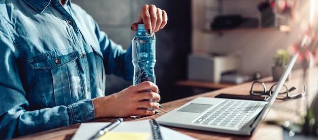 Vrouw het openen fles water in het bureau