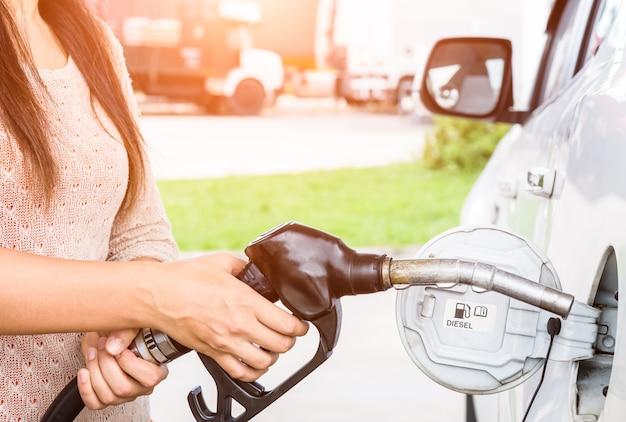 Vrouw het pompen benzinebrandstof in auto bij benzinestation.