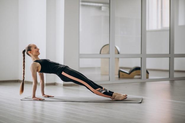 Vrouw het praktizeren yoga in de gymnastiek op een mat
