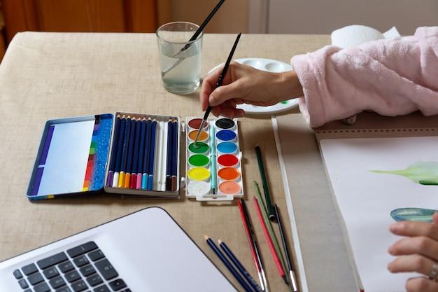 Vrouw het schilderen met waterverven thuis