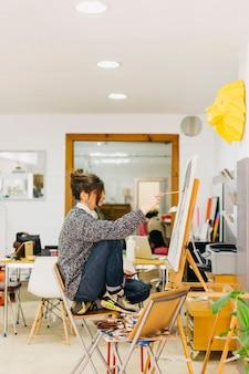 Vrouw het schilderen portret in atelier
