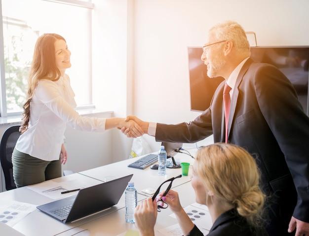 Vrouw het schudden hand met hogere zakenman na het beëindigen van de vergadering