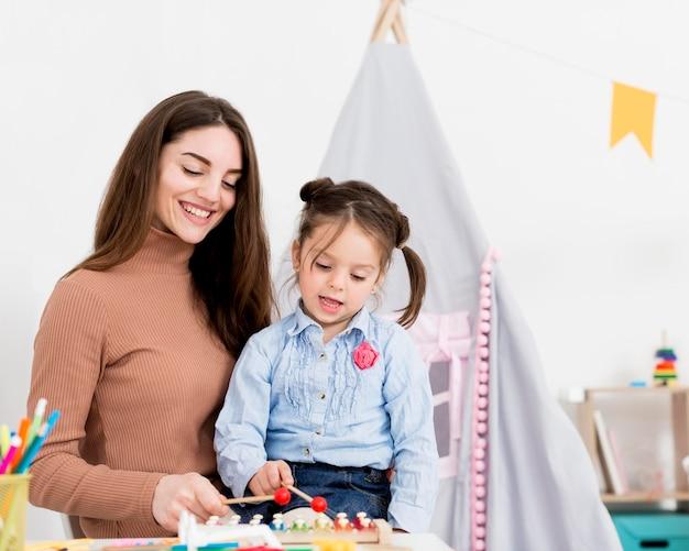 Vrouw het spelen met jong meisje thuis