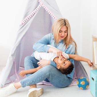 Vrouw het spelen met jonge jongen naast tent