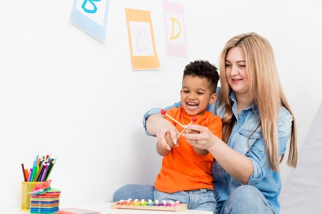 Vrouw het spelen met jonge jongen thuis