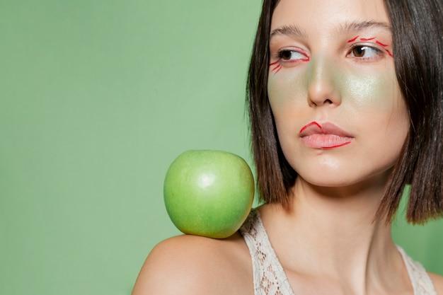Vrouw het stellen met appel op schouder