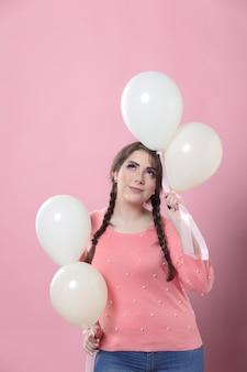 Vrouw het stellen met ballons terwijl omhoog het kijken