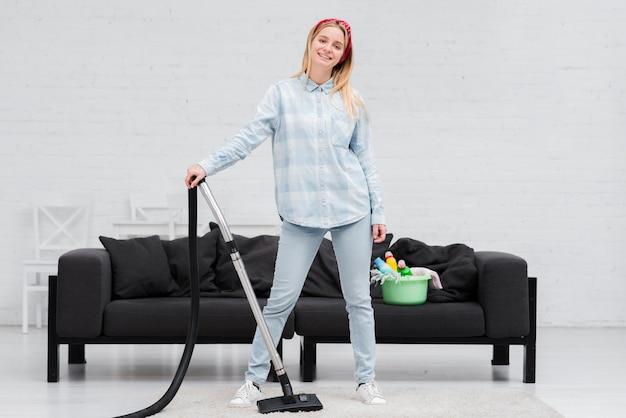 Vrouw het stellen met stofzuiger