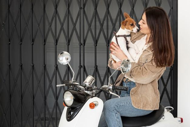 Vrouw het stellen op autoped terwijl het houden van haar hond