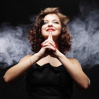 Vrouw het stellen over rookachtergrond