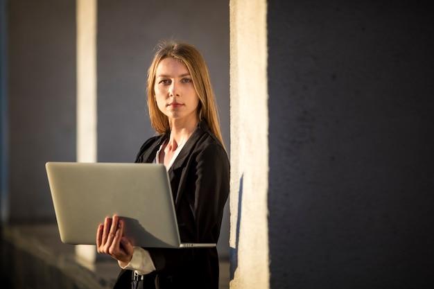 Vrouw het stellen voor camera die laptop houdt