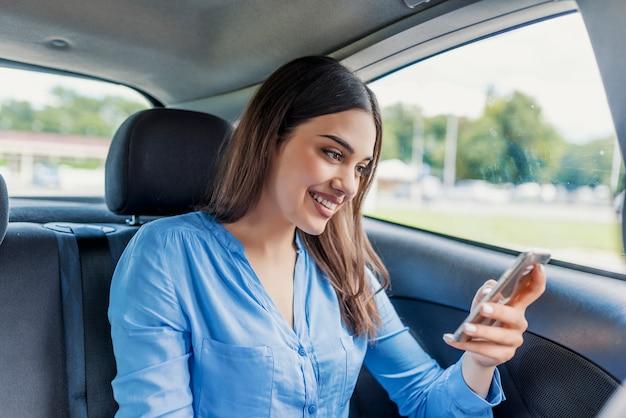 Vrouw het typen de sociale netwerken van het tekstbericht op smartphone terwijl het reizen door auto