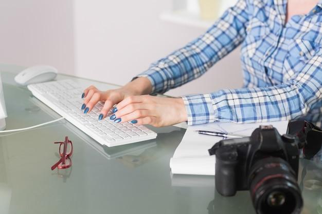 Vrouw het typen op toetsenbord bij haar bureau