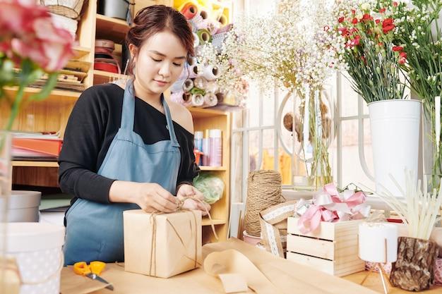 Vrouw het verpakken stelt in bloemenwinkel voor