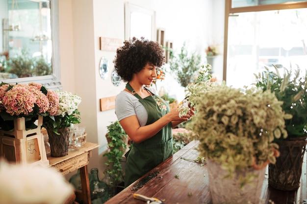 Vrouw het verzorgen van bloemen in bloemenwinkel