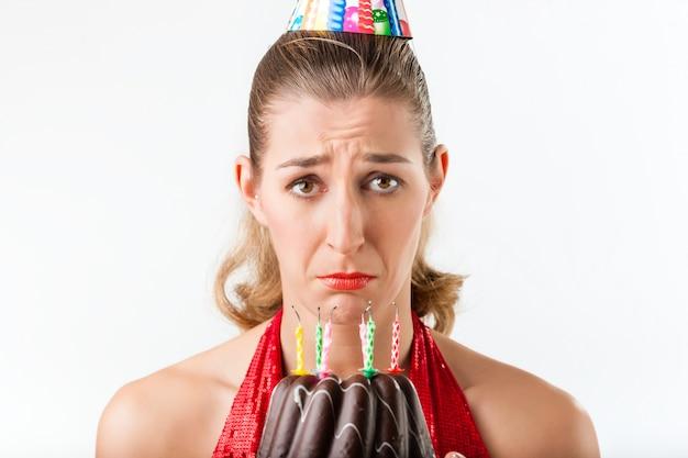 Vrouw het vieren verjaardag met geveegde cakekaarsen