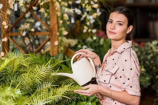 Vrouw het water geven installatie in groen huis
