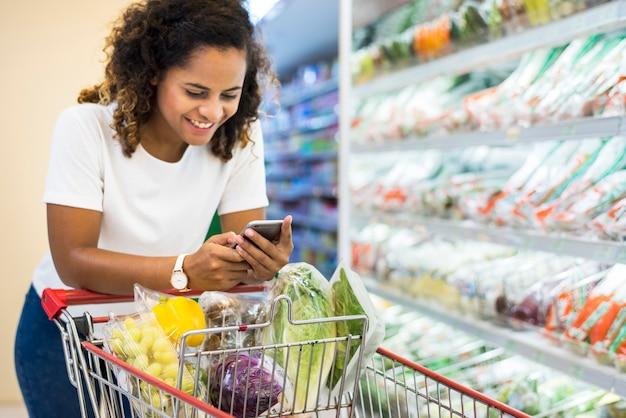 Vrouw het winkelen groenten bij de supermarkt