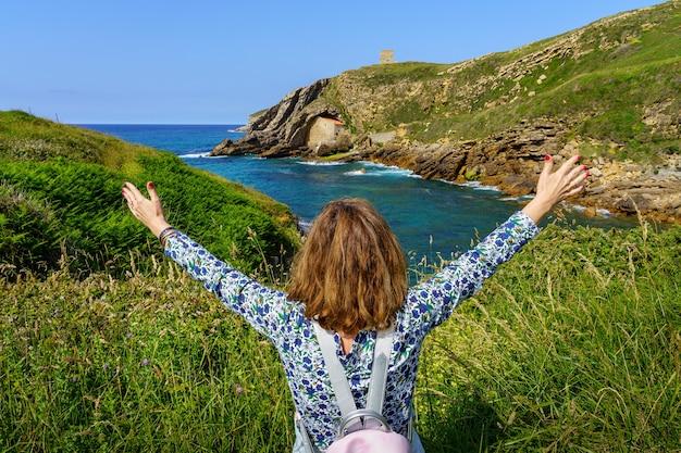 Vrouw hief haar armen in geluk kijkend naar het zeegezicht