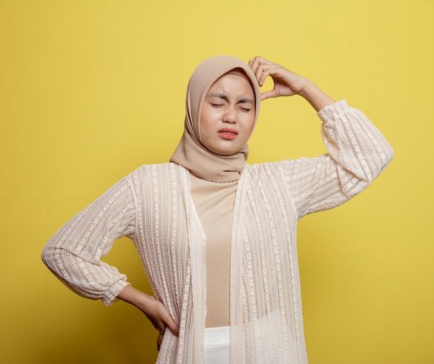 Vrouw hijab met een duizelige uitdrukking die iets denkt dat het hoofd houdt dat op gele achtergrond wordt geïsoleerd
