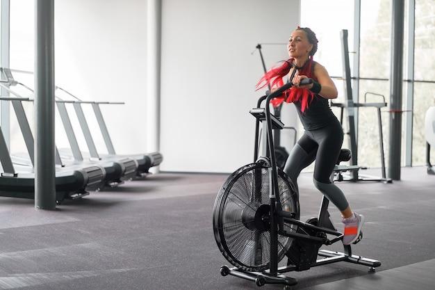 Vrouw hometrainer sportschool fietsen training fitness.