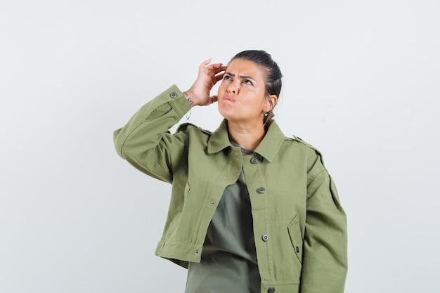 Vrouw hoofd krabben in jasje, t-shirt en aarzelend op zoek