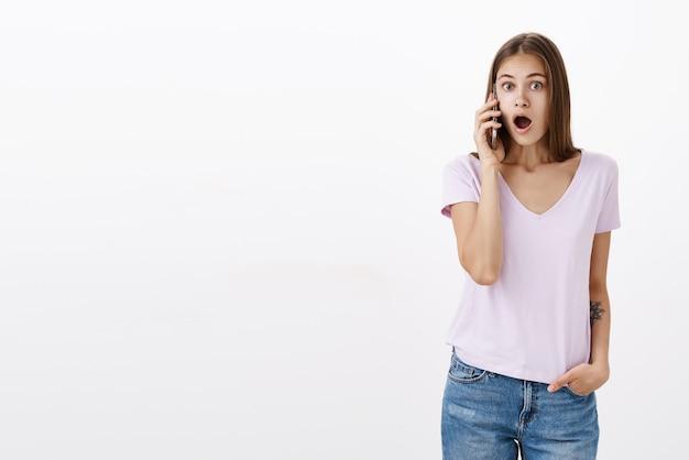 Vrouw hoort de laatste verse en opmerkelijke geruchten praten aan de telefoon, geschokt en verbaasd terwijl ze de mond opent van verbazing en verrassing terwijl ze smartphone in de buurt van oor houdt