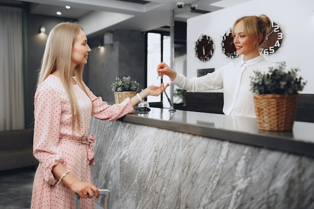 Vrouw hotelgast sleutelkaart ontvangen van receptioniste