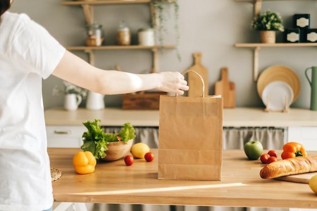 Vrouw houd eco boodschappentas met verse groenten en stokbrood in moderne keuken