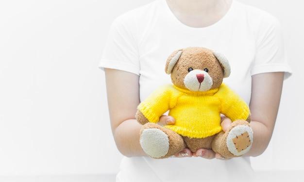 Vrouw houden en beschermen geven een bruine teddybeer speelgoed dragen gele shirts zittend op een witte achtergrond close-up, symbool van liefde of dating