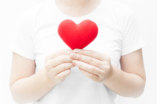 Vrouw houden en beschermen van een rood hart vorm op witte achtergrond close-up, symbool van liefde of dating valentijnsdag