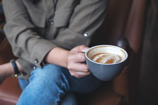 Vrouw houden en hete latte koffie drinken zittend in café