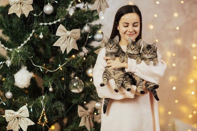 Vrouw houden en kijken naar haar drie kittens