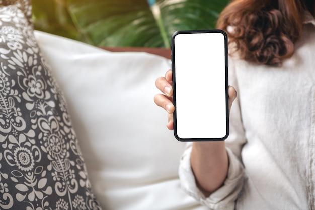 Vrouw houden en zwarte mobiele telefoon met leeg wit scherm op de tafel in het moderne café tonen Premium Foto