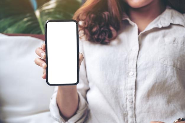 Vrouw houden en zwarte mobiele telefoon met leeg wit scherm op de tafel in het moderne café tonen