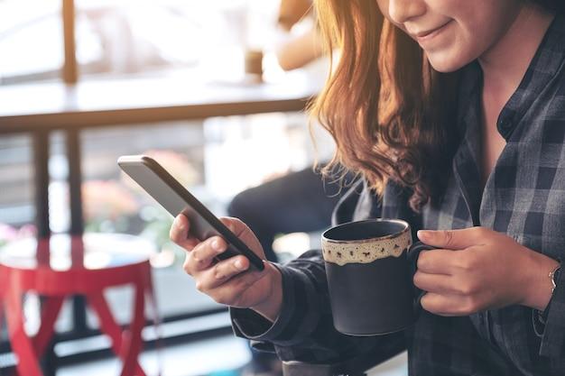 Vrouw houden, gebruiken en kijken naar slimme telefoon tijdens het drinken van koffie in café