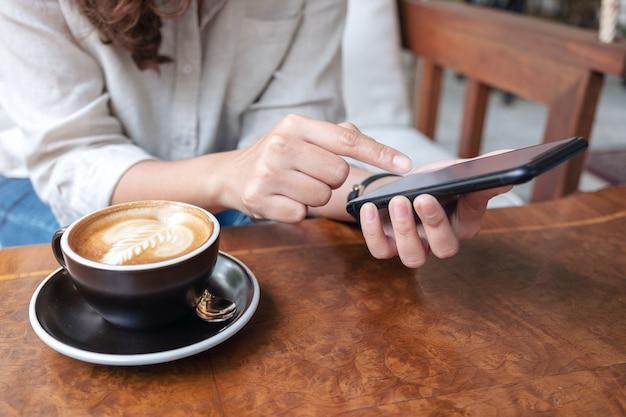 Vrouw houden, gebruiken en wijzende vinger op slimme telefoon tijdens het drinken van koffie in café